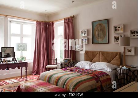 Rosa Nicole Fabre Stock Länge Gardinen im Schlafzimmer mit Peddigrohr Kopfteil, gerahmte Schmetterling Kunst und - Stockfoto