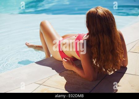 Hübsche junge Dame Swimming Pool liegen und ein Sonnenbad zu genießen. Weibliches Model tragen Bikini Sonnenbaden - Stockfoto