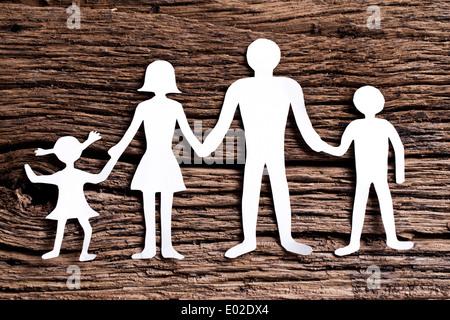 Pappfiguren der Familie auf einem Holztisch. Das Symbol der Einheit und des Glücks. - Stockfoto