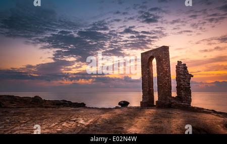 Sonnenuntergang über dem Meer und felsigen Küste mit antiken Ruinen und Tor nach Afrika in Mahdia, Tunesien - Stockfoto