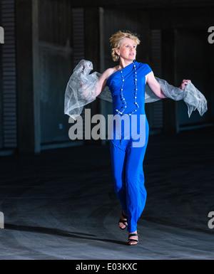 Verängstigte Frau trägt blaues Kleid und laufen im öffentlichen Parkhaus - Stockfoto