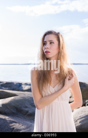 Schöne junge Frau trägt weißes Kleid, skandinavischen Küste und Meer im Hintergrund - Stockfoto