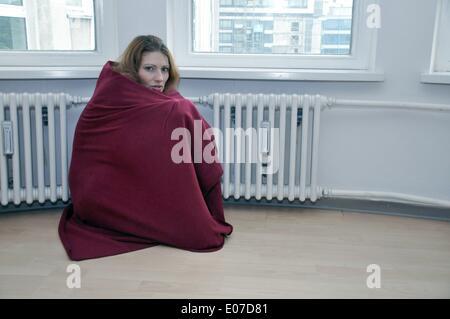 ILLUSTRATION - eine Frau in einer roten Decke wärmt sich bei einer Erhitzung auf 27. Juni 2012. Foto: Berliner Verlag/Steinach - Stockfoto