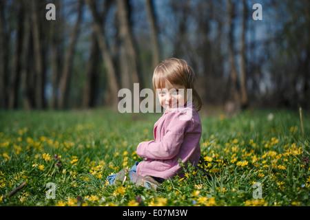Kleines Mädchen sitzt auf Wiese - Stockfoto