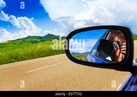 Fotograf in Autospiegel fährt in der Nähe von Tal - Stockfoto