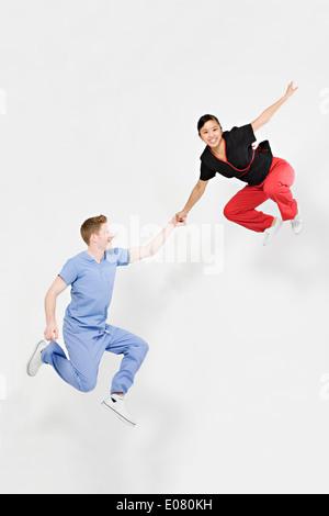 Medizinische Tanzpaar springt gerne in Scrubs – Die Anfänger weiß nahtlose Hintergrund - Stockfoto
