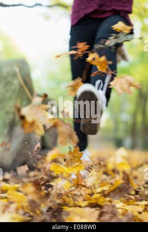 Geringen Teil der Teenager-Mädchen läuft durch gefallene Ahorn Blätter - Stockfoto