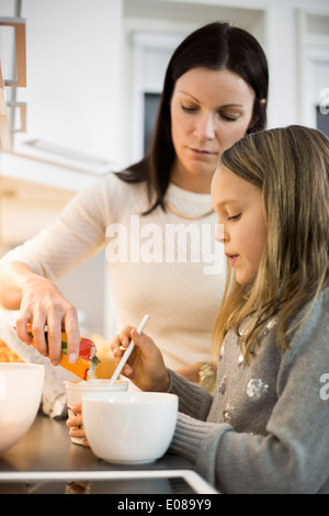 Mutter und Tochter hinzufügen Geschmack im Cup in Küche - Stockfoto