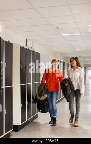 Voller Länge der glückliche Mädchen im Teenageralter zu Fuß im High-School-Korridor - Stockfoto