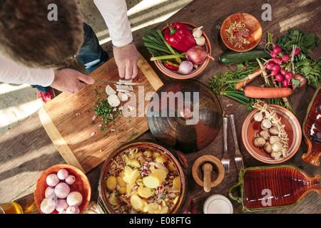 Mann schneiden Zwiebeln neben Vielfalt an Gemüse - Stockfoto