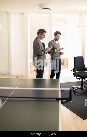 Geschäftsleute, die Benutzung von Mobiltelefonen im Büro - Stockfoto