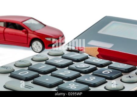 Ein Auto und einen roten Stift liegt auf einem Taschenrechner. Wenn Kosten Fue Benzin, Abnutzung und Qualitätssicherung. - Stockfoto