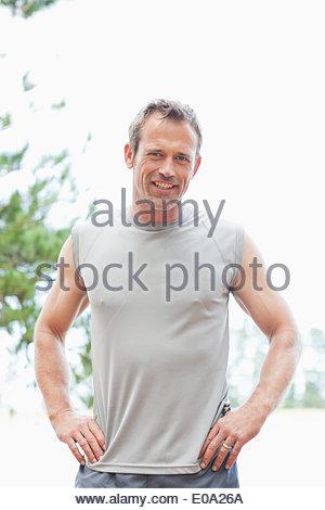 Mann mit Händen auf den Hüften lächelnd - Stockfoto