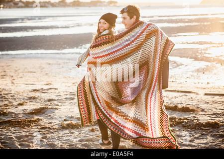 Paar, eingewickelt in eine Decke, ein Spaziergang am Strand - Stockfoto
