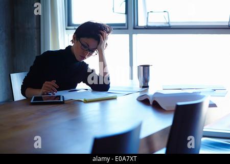 Junge Unternehmerinnen betonte mit Papierkram im Büro - Stockfoto