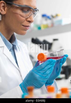 Weibliche Zellbiologe hält ein Fläschchen mit Stammzellen, kultiviert in roten Wachstumsmedium, um Krankheit zu - Stockfoto