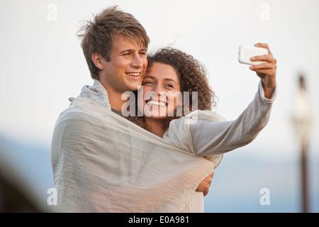Junges Paar unter Bild von sich selbst - Stockfoto