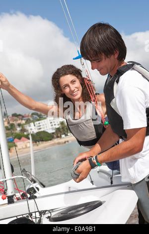 Zwei junge Freunde, die unter Vorbereitung Segelboot im Hafen - Stockfoto
