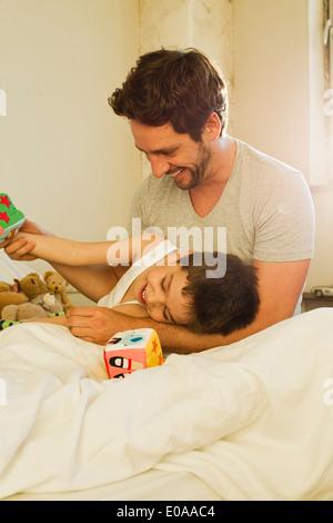 Vater und seinem kleinen Sohn spielen auf Bett - Stockfoto