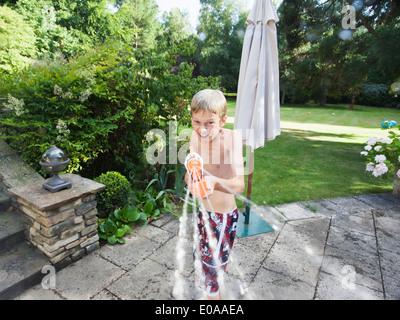 jungen kind spielt mit einem schlauch in einem vorst dtischen garten im sommer mit einem. Black Bedroom Furniture Sets. Home Design Ideas