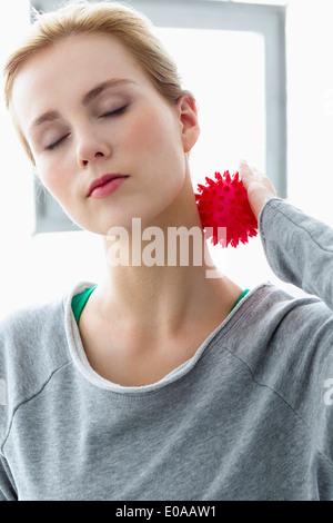 Junge Frau mit Massage-Ball am Hals - Stockfoto