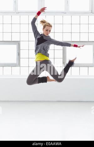 Junge Frau im Gymnasium springen - Stockfoto