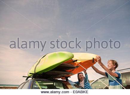 Mutter und Sohn Stapeln Kajaks auf Auto - Stockfoto