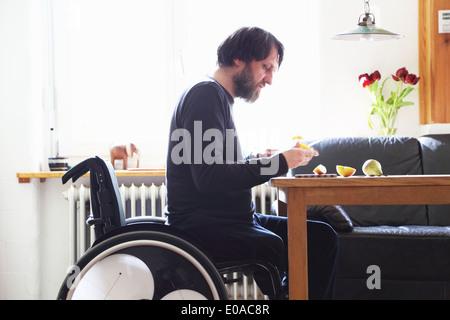 Mann im Rollstuhl Schneiden Früchte - Stockfoto
