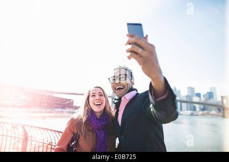 Junges Paar nehmen Selfie mit Brooklyn Bridge, New York, USA - Stockfoto