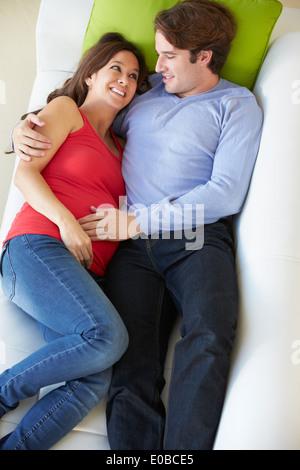 Draufsicht des Menschen entspannend auf Sofa mit schwangeren Frau - Stockfoto