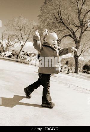 Schwarzen & weiße Foto von 16 Monaten kleine Mädchen spielen auf einem Park-Spielplatz