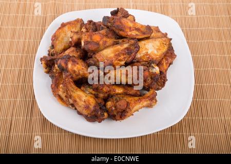 Gebratene Hähnchenflügel mit Mesquite-Sauce auf einem weißen Teller - Stockfoto