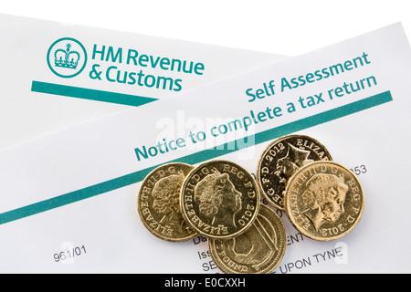 UK HM Revenue & Zoll selbst Steuerbescheid eine Steuererklärung mit ein paar Pfund-Münzen auf weiß abgeschlossen. - Stockfoto