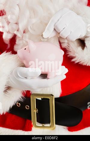 Mittleren Bereich des Weihnachtsmanns, Münze im Sparschwein - Stockfoto
