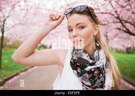 Attraktive junge weibliche Model posiert im Frühlingspark. Lässige jungen Frau mit Sonnenbrille und Halstuch Blick - Stockfoto