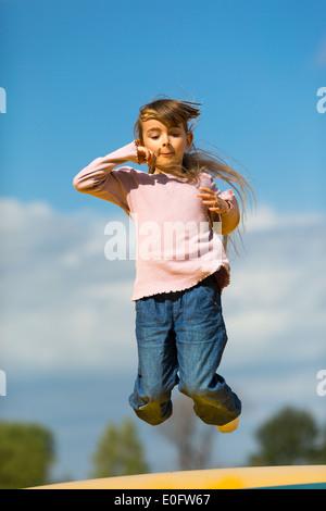 Mädchen auf und ab hüpfte auf bouncy Kissen im Freien im Frühling. - Stockfoto