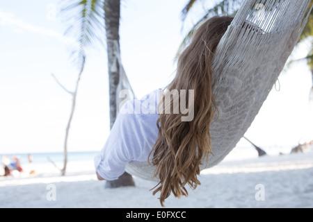 Frau mit langen Haaren zum Entspannen in der Hängematte über Sand mit Blick auf Meer unter Palmen in Tulum Beach, - Stockfoto