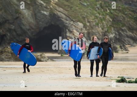 Vier Surfer Strandspaziergang hält ihre Surfbretter in Newquay, Cornwall, England. - Stockfoto