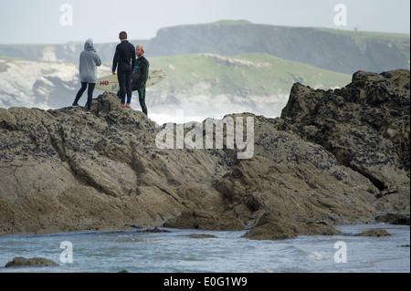 Drei Jugendliche stehen auf einem Felsen in Newquay, Cornwall, England. - Stockfoto