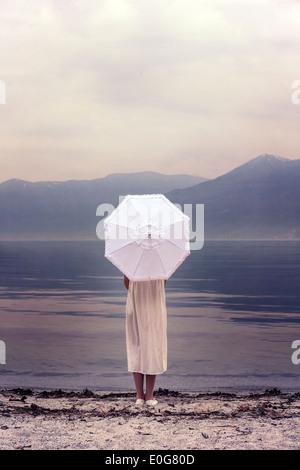 ein Mädchen mit einem Sonnenschirm am Strand - Stockfoto