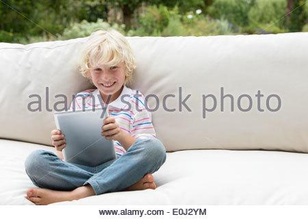 Porträt eines lächelnden jungen mit digital-Tablette auf Outdoor-sofa - Stockfoto