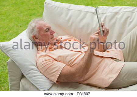 Senior woman outdoor-Sofa auflegen und mit digital-Tablette - Stockfoto