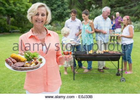 Porträt des Lächelns senior Frau Halteblech Grill und Wein mit Familie im Hintergrund - Stockfoto