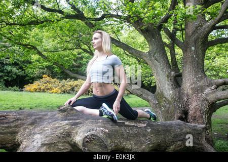 Blonde Dame tragen schwarze Leggings und ein grauer Ernte praktizieren Yoga im Zentrum von einem Baum auf Hampstead - Stockfoto
