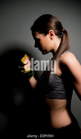 Junge Frau trägt Sport/Fitness Top Kick-Box-Handschuh mit geballter Faust gegen einen grauen Hintergrund mit dunklen - Stockfoto