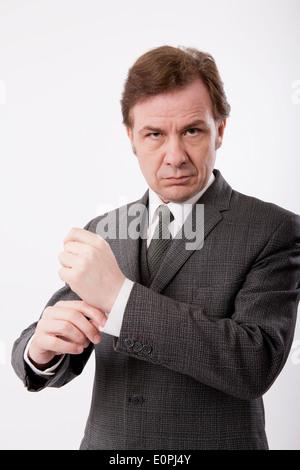Mann in einem grauen klassischen Business Anzug sein Hemd Manschette, vor einem weißen Hintergrund anpassen. - Stockfoto