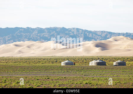 Jurten und Gers, auf der grünen Steppe vor der großen Sanddünen der Khongoryn Els, Gobi-Gurvansaikhan-Nationalpark - Stockfoto
