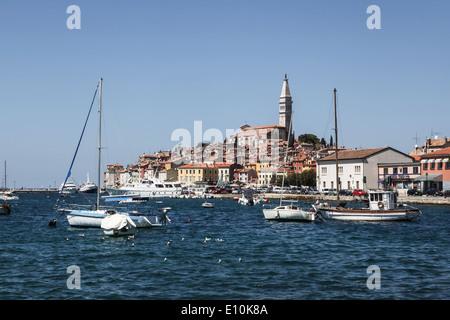 Altstadt von Rovinj in Kroatien, mit Bell Turm von St. Euphemia Basilika, Stadtgebäude und Marina mit Segelbooten - Stockfoto