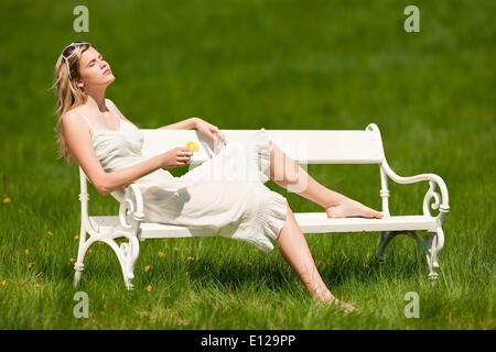 22. April 2009 - 22. April 2009 - Frühling und Sommer - junge Frau in Wiese auf weißen Bank an sonnigen Tag entspannend: - Stockfoto