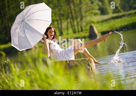 5. Juni 2010 - 5. Juni 2010 - Happy romantische Frau See Spritzwasser, hält Sonnenschirm, weißen Kleid - Stockfoto